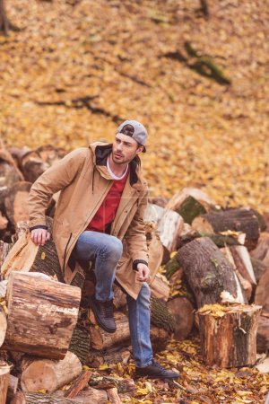 Young man sitting on dry stumps