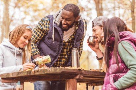 Photo pour Groupe d'amis souriants assis à une table en bois et versant une boisson chaude dans la forêt d'automne - image libre de droit