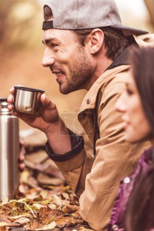 Photo for Side view of handsome young man sitting near brunette woman and holding cup from thermos with hot drink - Royalty Free Image
