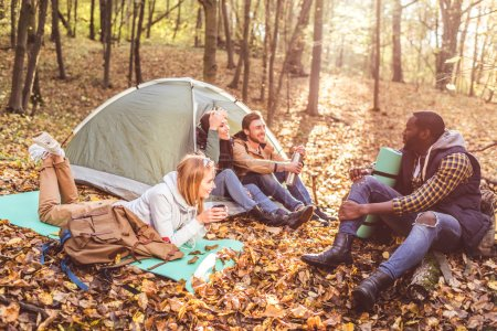 Photo for Young friends travelers sitting and talking near tent in autumn forest - Royalty Free Image