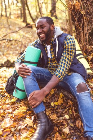 Photo for Portrait of handsome smiling man with backpack sitting on tree root and looking away in autumn forest - Royalty Free Image