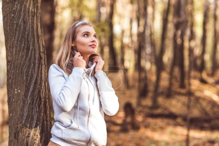 Young beautiful woman in autumn forest