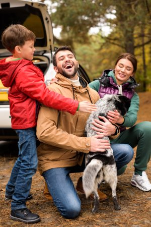 Happy family playing with dog in forest