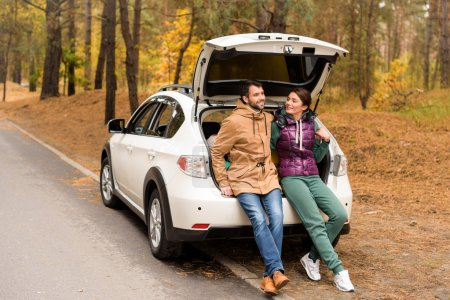 Photo for Smiling young couple sitting in open car trunk in autumn forest - Royalty Free Image