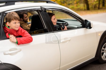 Photo for Cute smiling boy looking through car window while traveling with parents in autumn forest - Royalty Free Image