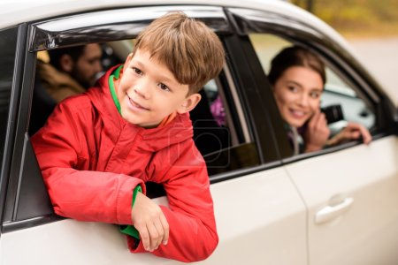 Smiling boy looking through car window