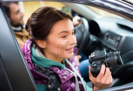 Photo for Smiling brunette woman holding photo camera and looking in car window with blurred male driver - Royalty Free Image