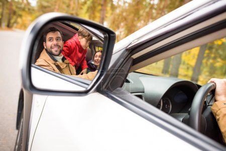 Photo for Happy family reflected in a car mirror in autumn forest - Royalty Free Image