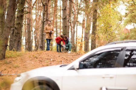 Photo for Smiling man photographing beautiful woman and boy playing with dog in autumn forest - Royalty Free Image