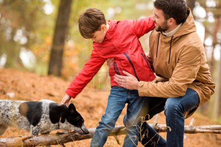 Photo for Happy boy playing with smiling father and dog in autumn forest - Royalty Free Image
