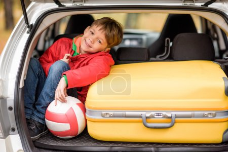 Smiling boy sitting in car trunk
