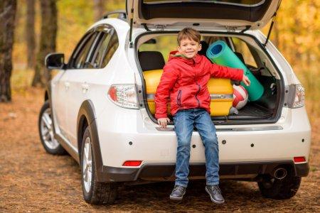 Photo pour Petit garçon souriant assis dans un coffre de voiture ouvert avec balle et bagages - image libre de droit