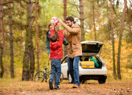 Photo for Happy family playing with ball and having fun during family trip in autumn forest - Royalty Free Image