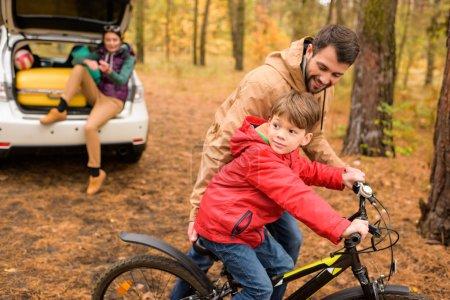 Photo pour Père heureux apprenant à son fils à faire du vélo dans la forêt d'automne - image libre de droit