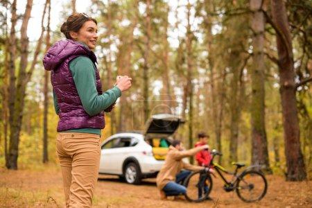 Photo pour Femme souriante debout avec thermos dans la forêt d'automne et père enseignant fils équitation vélo - image libre de droit