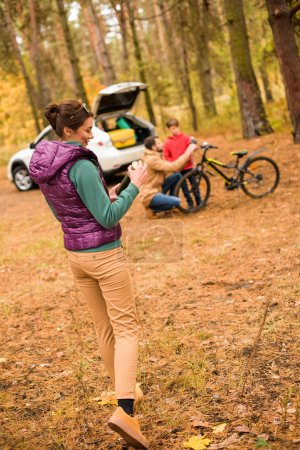 Photo for Smiling woman standing with thermos in autumn forest and father teaching son riding bicycle - Royalty Free Image