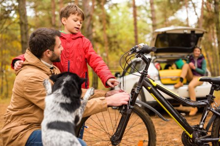 Photo for Happy father teaching his son to ride a bicycle in autumn forest - Royalty Free Image