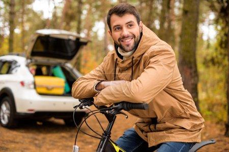 Smiling man sitting on bicycle