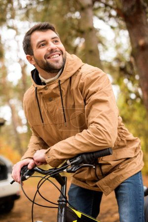 Smiling man sitting on bicycle
