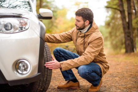 Photo for Young bearded man checking car tyre in autumn forest - Royalty Free Image