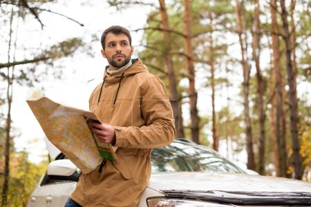 Man holding map and leaning on car