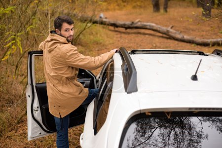 Man standing near car and fallen tree