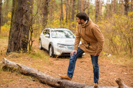 Man standing on dry log in forest