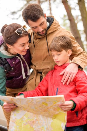 Photo pour Famille debout avec carte près de la voiture blanche dans la forêt d'automne - image libre de droit