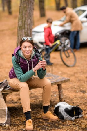 Smiling woman with hot drink in forest