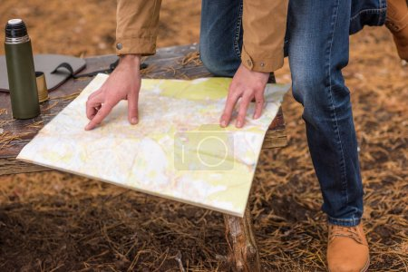 Male hands and map in forest