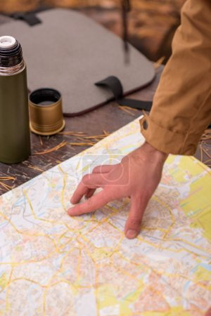 Male hand and map in forest