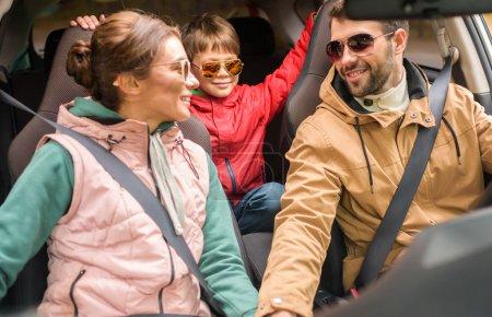 Foto de Happy friendly family travelling by car on rural road - Imagen libre de derechos