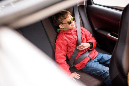 Photo pour Garçon souriant, assis sur le siège arrière de voiture verrouillée avec la ceinture de sécurité et profiter des vacances en famille voyage - image libre de droit