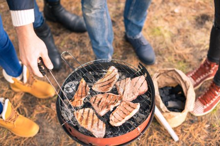 Photo for Close-up view of young people grilling meat on a charcoal grill outdoors - Royalty Free Image