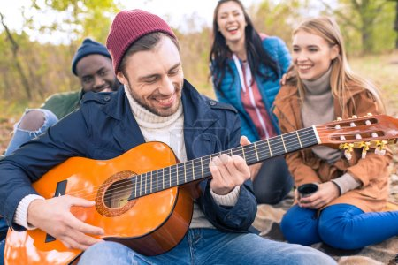 Friends enjoying guitar in autumn park