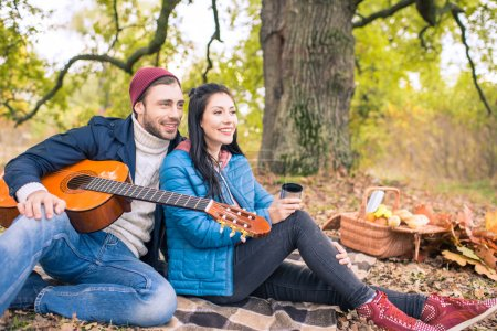 Photo for Happy romantic couple sitting on plaid and enjoying guitar in autumn forest - Royalty Free Image