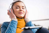 Beautiful woman in headphones listening music