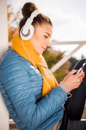 Photo for Close-up portrait of beautiful young woman wearing white headphones and listening music with smartphone - Royalty Free Image