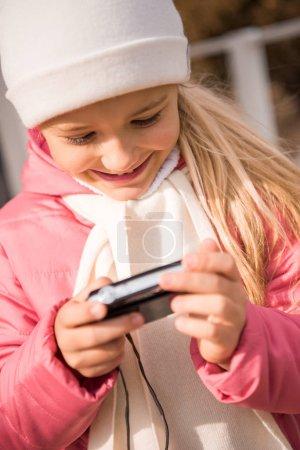Smiling girl holding photo camera