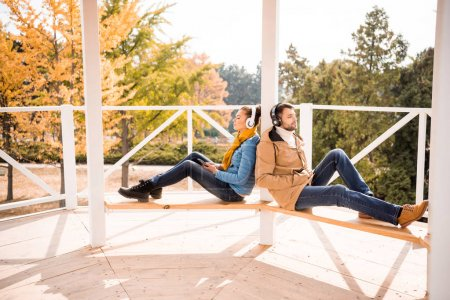 Photo pour Beau jeune couple assis sur un banc en bois dans un casque à la journée ensoleillée d'automne - image libre de droit