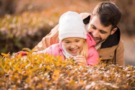 Photo for Close-up portrait of adorable little girl playing with smiling father in autumn park - Royalty Free Image