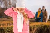 Sad little girl standing outdoors