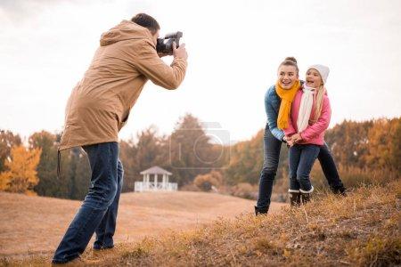 Photo pour Jeune homme photographier l'heureuse mère et fille avec appareil-photo instantané à l'extérieur - image libre de droit