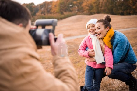 Man photographing happy mother and daughter