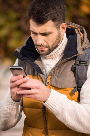 Photo for Close-up portrait of thoughtful young bearded man looking at smartphone outdoors - Royalty Free Image