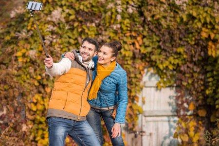 Photo pour Beau couple souriant prenant selfie au jour ensoleillé d'automne - image libre de droit