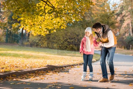 Photo for Happy father teaching little daughter to roller skating in autumn park - Royalty Free Image