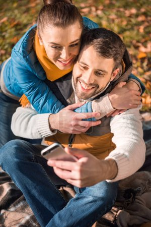 Beautiful smiling couple looking at smartphone