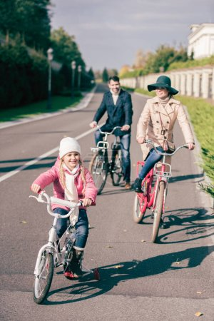 Photo for Cheerful family biking in park at sunny autumn day - Royalty Free Image