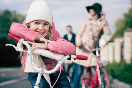 Cute little girl sitting on bicycle